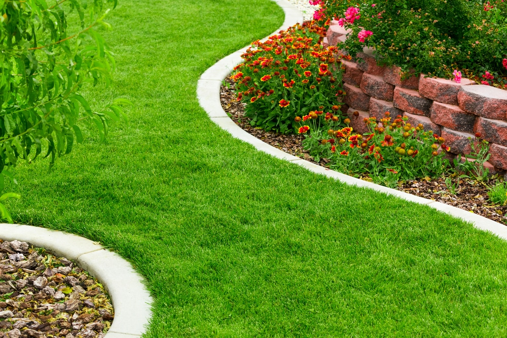 stunning lush green lawn separated by stone garden edging
