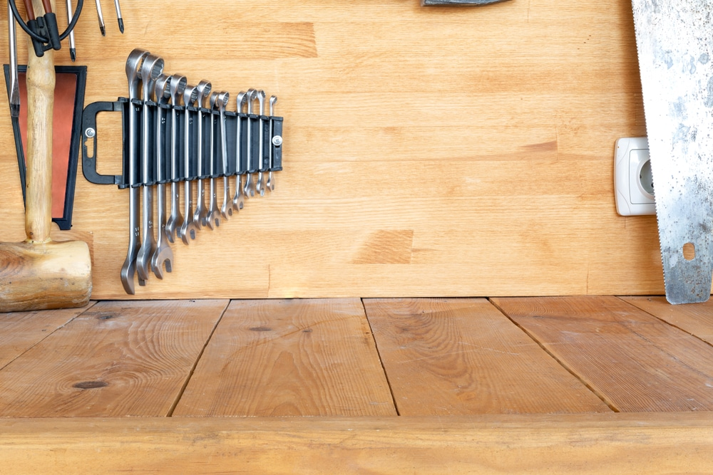surface of a workbench with tools hung up in background