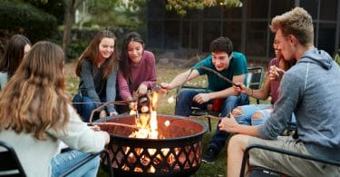 teenagers sat around a garden fire pit