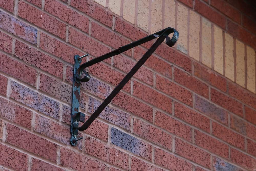 metal holder for hanging basket on outside wall