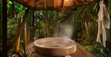steaming hot tub under a wooden canopy