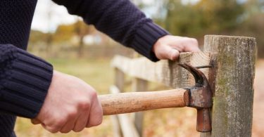 man using hammer to remove nail from a fence